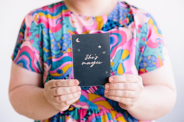 "Ali holding ""She's magic"" postcard"